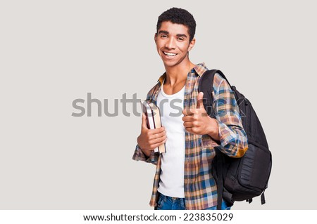 Being a student is cool! Handsome young Afro-American student holding books and stretching out hand with thumb up while standing against grey background - stock photo