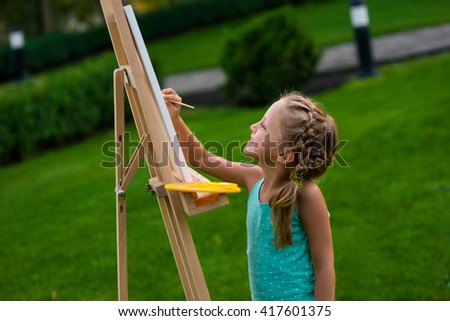 Being busy with hobby. Little smiling girl is improving her talant of a painter by trying to create a worthy drawing on the easel. Perfect retouching of the photo. - stock photo