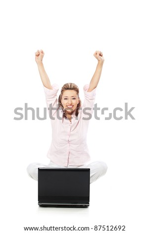 Being happy and satisfied / Smiling woman sitting in front of laptop with arms raised isolated - stock photo