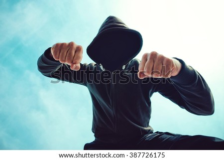 Being punched and mugged by aggressive violent man in hooded jacket on street, victim's pov perspective. - stock photo