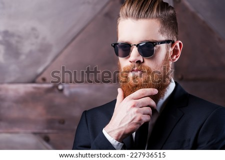 Being stylish is on my mind. Close-up of a confident young man in shirt and tie holding hand on his chin   - stock photo