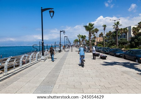 BEIRUT, LEBANON - JUNE 16, 2013: An unidentified locals walk along the beach around quay. Life in Beirut is coming back to normal after Lebanon war in 2006. - stock photo