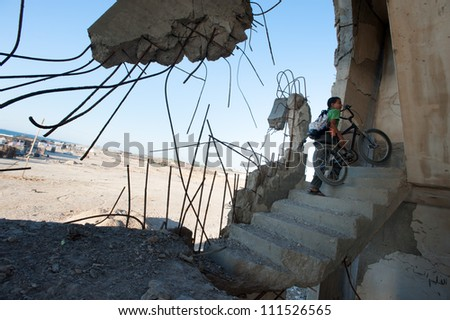 BEIT LAHIA, GAZA - JULY 4: Palestinian children stand among the ruins of buildings in Beit Lahia, Gaza, destroyed by Israeli air strikes in the 2008-2009 war known as Operation Cast Lead, July 4, 2012 - stock photo