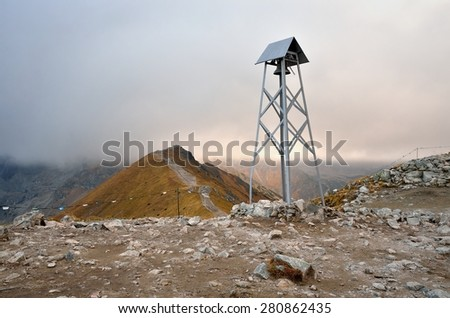 Belfry in mountains. A simple belfry at the top of Kasprowy Wierch in Tatra mountains in Poland. - stock photo