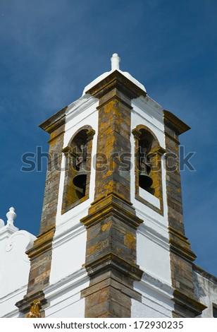 Belfry of Monsaraz across from the square from the Parochial church of Nossa Senhora da Lagoa - stock photo