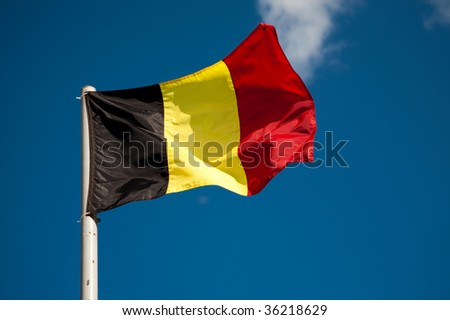 Belgian flag against blue sky - stock photo