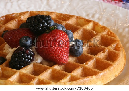 belgian waffle with assorted berries, syrup, and whipped cream on top - stock photo