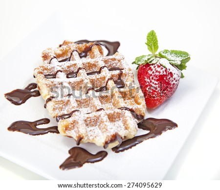 Belgian waffle with powdered sugar and chocolate syrup - stock photo