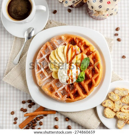 Belgian waffles with bananas and whipped cream, decorated with caramel sauce and powdered sugar on the table with a cup of coffee, coffee beans with cinnamon and two glass jars - stock photo