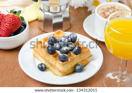Belgian waffles with blueberries, coffee and orange juice for breakfast - stock photo