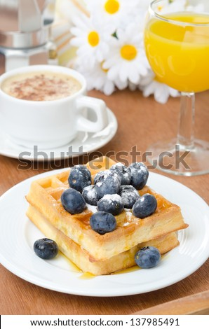 Belgian waffles with blueberries, coffee and orange juice for breakfast vertical - stock photo