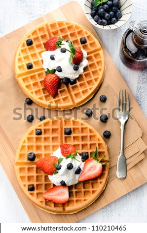 Belgian waffles with blueberries, strawberries and maple syrup - stock photo