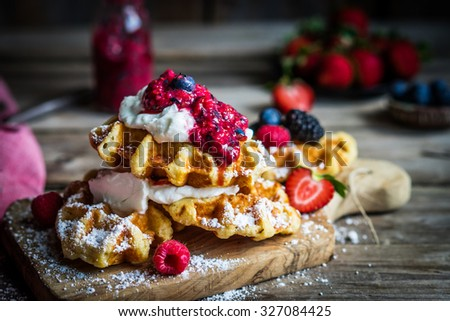 Belgian waffles with fresh berries on rustic wooden background - stock photo