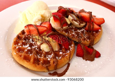 Belgian waffles with ice cream, chocolate and strawberries - stock photo