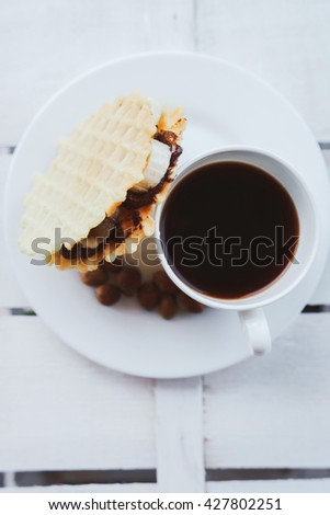 Belgian waffles with peanut butter, hazelnuts on a wooden background. Delicious breakfast with espresso. Vertical view - stock photo