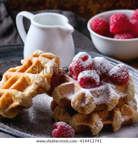 Belgian waffles with raspberries and sugar powder, served with jug of milk on vintage metal tray with textile napkin over rusty surface. Dark rustic style. Square image with selective focus - stock photo