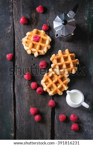 Belgian waffles with raspberries, served with coffee pot and jug of milk over old wooden table. Flat lay - stock photo