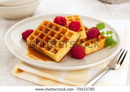 belgian waffles with syrup or caramel sauce served on a plate, garnished with raspberries and mint - stock photo