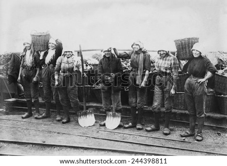Belgian women coal miners dressed in trousers. They wear workers' clogs and headscarves, and tight belts that emphasize their waists. Between 1900-1920. - stock photo
