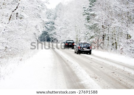 Belgium in winter, cars driving over a snow covered street - stock photo