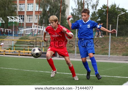 BELGOROD, RUSSIA - AUGUST 20: Unidentified boys plays football on August, 20 2010 in Belgorod, Russia. The final of Chernozemje superiority, Football kinder team of 1996 year of birth. - stock photo
