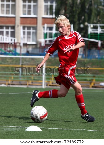 BELGOROD, RUSSIA - JULY 7: Unidentified boy plays football July, 7 2010 in Belgorod, Russia. The final of Chernozemje superiority, Football kinder team of 1998 year of birth. - stock photo