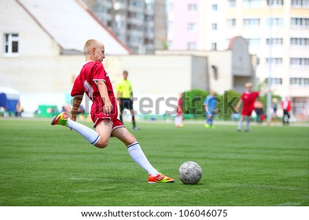 "BELGOROD, RUSSIA - JUNE 17: Unidentified boy from football team ""Oriol"" making pass on June 17, 2012 in Belgorod, Russia. Chernozemie Superiority. Football team of 2001 year of birth. - stock photo"