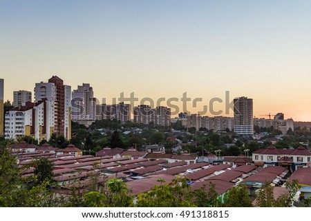 "BELGOROD, RUSSIA - SEPTEMBER 10, 2016: Neighborhood of low-rise residential buildings with multi-storey buildings on a slope. Old street market ""Salut"". Evening skyline. Cityscape Belgorod, Russia."