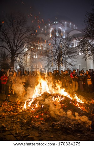 BELGRADE - JANUARY 6: People watch a ceremonial burning of dried oak branches - the Yule log symbol for the Orthodox Christmas Eve in front of St. Sava church on January 6, 2014 in Belgrade, Serbia.