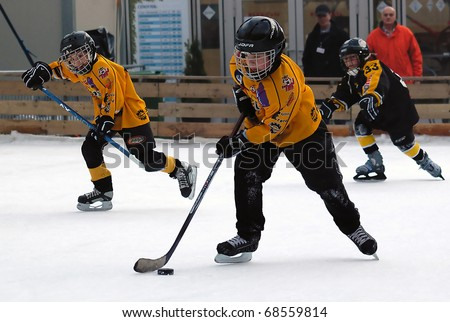 BELGRADE-JANUARY 8:Unidentified ice hockey players in action with puck at New Year's ice hockey tournament for children aged eight years on January 8, 2011 in BELGRADE,SERBIA - stock photo