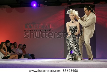 BELGRADE - JUNE 26: Hairstylist Claude Tarantino is doing hairstyle on model during L'Oreal professional presentation on Brand Fair on June 26, 2006 in Belgrade, Serbia. - stock photo