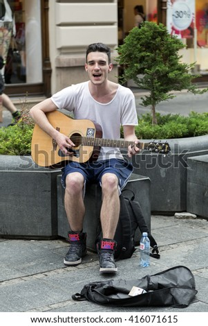 Belgrade, Serbia - April 17, 2016: A young male street musician performing with his guitar in a square in Belgrade, the Serbian capital on April 17. - stock photo