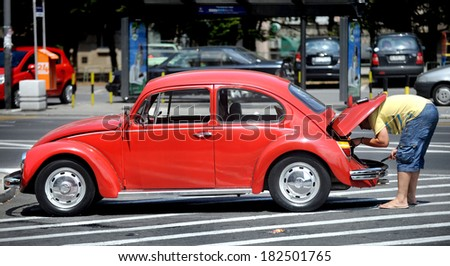 BELGRADE, SERBIA - CIRCA JULY 2008: A man attempts to recover car failure, circa July 2008 in Belgrade - stock photo