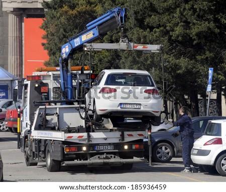 BELGRADE, SERBIA - CIRCA MARCH 2014: Tow truck takes away illegal parked car, circa March 2014 in Belgrade - stock photo