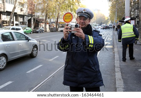 BELGRADE, SERBIA - CIRCA NOVEMBER 2011: Unidentified police officer films traffic violation, circa November 2011 in Belgrade. - stock photo
