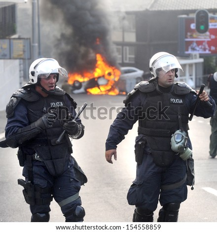 """BELGRADE, SERBIA - CIRCA OCTOBER 2010: Special force policeman watches burning police car after riots at """"Belgrade Pride"""" circa October 2010 in Belgrade - stock photo"""