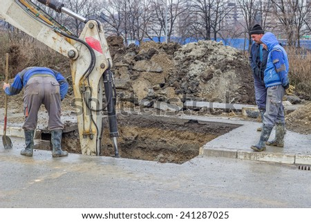 BELGRADE, SERBIA - DECEMBER 27: Excavator digging the ground, hunting for water leaks. Found the leaking in water pipes in December 2014.  - stock photo