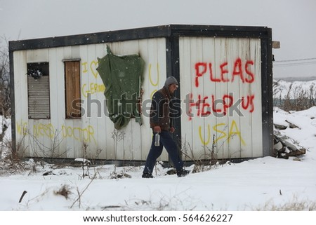 Belgrade, Serbia - January 18, 2017: Refugee passing the abandoned wagon with message help as USA in Belgrade, Migrant mostly from Afghanistan and Pakistan they seek ways to move on toward Western EU.