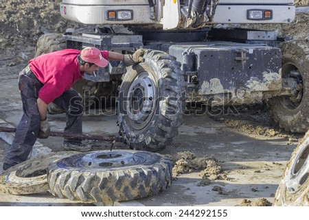 BELGRADE, SERBIA - JANUARY 13: Worker with iron lever changing a wheel of a excavator. Excavator tyre replacement. At construction site in January 2015.