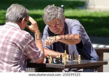 BELGRADE, SERBIA - JULY 29, 2014: two middle-aged men are playing a match of chess in Kalemegdan Fortress of Belgrade Old Town. Shot in 2014  - stock photo