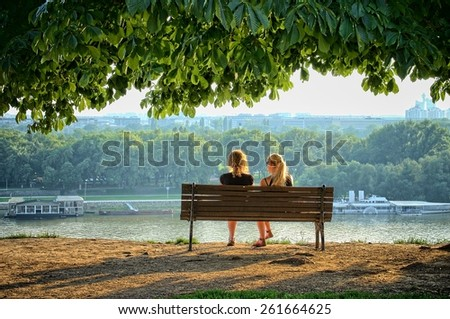 BELGRADE, SERBIA - JULY 29, 2014: two young women sitting on a bench of Kalemegdan Fortress in front the Danube rivers. Shot in 2014 - stock photo