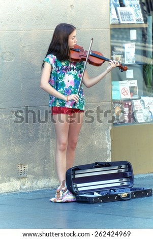 BELGRADE, SERBIA - JULY 29, 2014: young street musician is playing her violin in the Belgrade Old Town. Shot in 2014  - stock photo