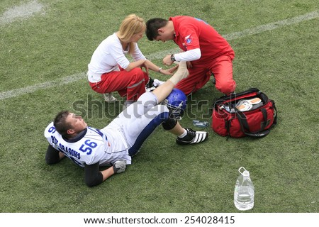Belgrade, Serbia - May 05, 2014: Doctors curling up leg injured player. American Football Match Between Belgrade Wolves And Blue Dragon in Belgrade. The Wolves team is winner. - stock photo