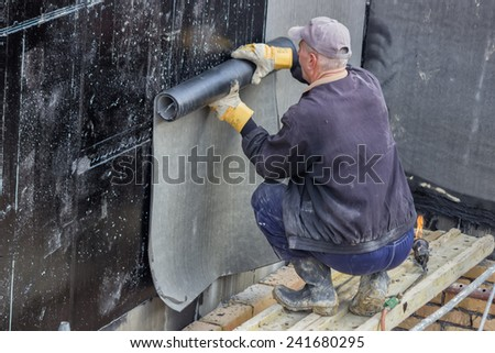 BELGRADE, SERBIA - NOVEMBER 24: Worker installing felt roll with heat torch on the basement concrete wall. At construction site in November 2014. - stock photo