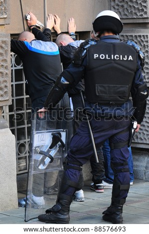 BELGRADE, SERBIA - OCTOBER 19: Policeman arrests two hooligans during protest of LGBT movement in Belgrade, Serbia, October, 19, 2011
