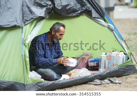 BELGRADE, SERBIA - SEPTEMBER 5 : A syrian refugee resting in a tent and eating while waiting for the transport to the European Union on September 5th, 2015 in Belgrade, Serbia.  - stock photo