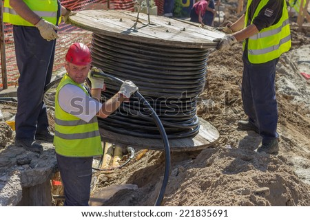 BELGRADE, SERBIA - SEPTEMBER 30:  Installing new ground infrastructure in the street. Workers unrolls electrical cable. Selective focus. At street Vojvode Stepe in September 2014. - stock photo