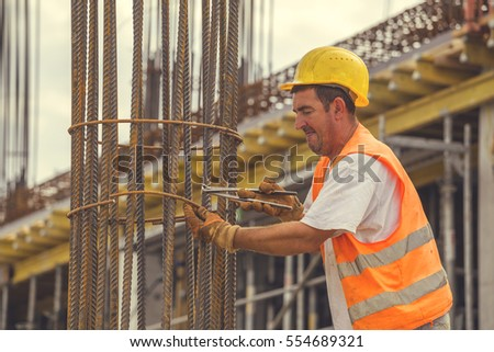 BELGRADE, SERBIA - SEPTEMBER 08, 2016: Tying reinforcing steel bars with plier and wire on construction pillars. Reinforcement work. Vintage style.