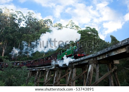 BELGRAVE - MAY 22: Historic Puffing Billy narrow guage steam train locomotive pulls carriages across trestle bridge in Sherbrooke Forest May 22, 2010 in Belgrave, Victoria, Australia. - stock photo