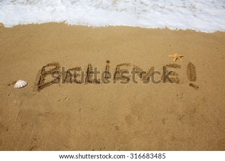Believe, a message written in the sand at the beach.